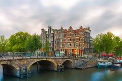 Skymningstadssikt av den Amsterdam kanalen och bron Royaltyfria Foton