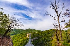 Skypark AJ Hackett Sochi, Adler, Russia - May, 2016. A metal pedestrian suspension bridge across the Mzymta River canyon in clear sunny weather against the Stock Photo
