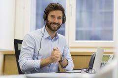 Счастливый бизнесмен в офисе на телефоне, шлемофон, Skype Стоковое фото RF