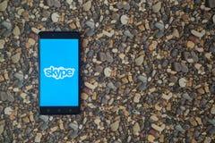 Skype-Logo auf Smartphone auf Hintergrund von kleinen Steinen Stockbilder