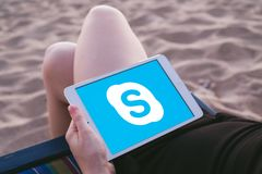 Koh Lanta, THAILAND - MARCH 18, 2018: Young woman at the beach with iPad in her hand showing Skype Logo stock photos