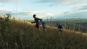 Skyrunning group of runners running uphill on blue sky background. Revda, Russia - September 10, 2016: skyrunning group of runners running uphill on blue sky stock footage