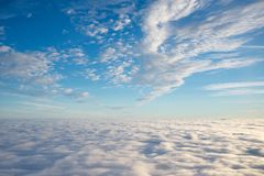 Skyscape above clouds, blue sky, white clouds. Skyscape as seen from plane with blue skies and white clouds Royalty Free Stock Photo