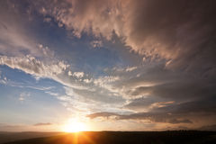 Skyscape background. Dramatic clouded skyscape with setting sun and stormy clouds Stock Photo