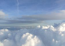 Skyscape - blue sky and thick white clouds; clouds texture. Skyscape - sky landscape with blue sky and thick white clouds seen from an airplane, dramatic look Royalty Free Stock Images
