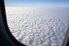 Skyscape with cloud from the plane window. Airplane wing on beautiful blue sky with cloud background royalty free stock photo