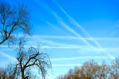 Skyscape with criss crossing vapour trails royalty free stock photos