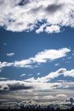 Skyscape med konturn av staden mot dramatiska moln Arkivbild