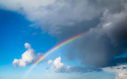 Skyscape view on blue sky with rainbow. Skyscape view on blue cloudy sky with colorful rainbow. Weather Royalty Free Stock Photo