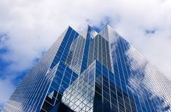 Skyscraper. Glass skyscraper against cloudy blue sky; strongly reflective windows; angular view from base Royalty Free Stock Image