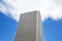 Skyscraper and blue sky with moving clouds Royalty Free Stock Photo