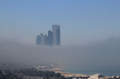 Skyscraper buildings on the coast surrounded by fog Royalty Free Stock Photo