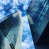 Skyscraper business buildings in blue sky with clouds. Royalty Free Stock Image