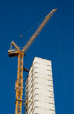 Skyscraper crane. A new skyscraper goes up with the help of a very tall crane Stock Images