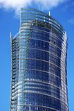 Skyscraper. Exclusive office building with original glass facade towering above the city. The facade is blue and is reflected in the sun. comfortable office will stock image