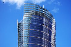Skyscraper. Exclusive office building with original glass facade towering above the city. The facade is blue and is reflected in the sun. comfortable office will royalty free stock photography