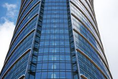Skyscraper. Exclusive office building with original glass facade towering above the city. The facade is blue and is reflected in the sun. comfortable office will royalty free stock image