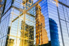 Skyscraper exterior reflection. Sunny summer skyline. Skyscraper exterior. Mirror reflection in glass facade of modern building. Orange and blue colors. Moscow royalty free stock photo
