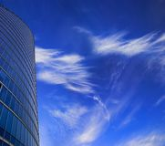 Skyscraper facade on blue sky. Office skyscraper facade on deep blue sky with white clouds. Place for copy space Royalty Free Stock Photos