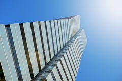 Skyscraper form below. Blue sky, sun flare and empty copy space Royalty Free Stock Photo