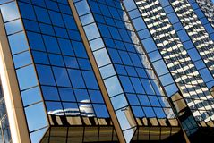 Skyscraper fragment. Reflections in a blue mirror glass wall of a skyscraper abstract background Royalty Free Stock Photos