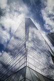 Skyscraper with glass facade and clouds reflected in windows Stock Photo