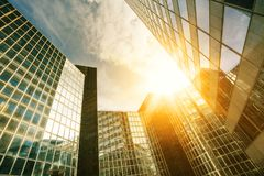 Skyscraper glass facades on a bright sunny day with sunbeams in the blue sky. Modern buildings in Paris business Stock Images