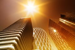 Skyscraper glass facades on a bright sunny day with sunbeams in the blue sky. Modern buildings in Paris business Royalty Free Stock Image