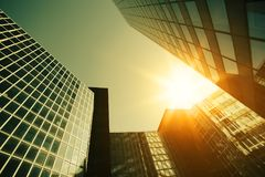 Skyscraper glass facades on a bright sunny day with sunbeams in the blue sky. Modern buildings in Paris business Royalty Free Stock Photo