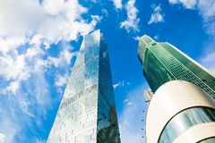 Skyscraper glass facades on a bright sunny day with sunbeams in the blue sky. Modern buildings in Moscow business district Stock Photos