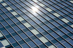 Skyscraper Glass Window Panel Office Building. With reflection of the sun shining on them Stock Image