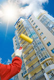 Skyscraper and house painter Stock Images
