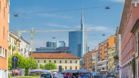 Skyscraper, modern and historic buildings in Milan timelapse. Street with shops and market. Cars on the street Via San Marco near church. Blue cloudy sky at stock video footage