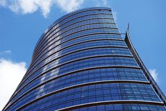 Skyscraper. NExclusive office building with original glass facade towering above the city. The facade is blue and is reflected in sun.City is proud of this stock image