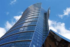Skyscraper. NExclusive office building with original glass facade towering above the city. The facade is blue and is reflected in sun.City is proud of this royalty free stock photos