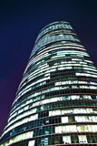 Skyscraper office building. Low angle view of rounded skyscraper office building illuminated at night Royalty Free Stock Photography