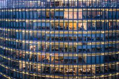 Skyscraper Office windows and office worker by night royalty free stock photos