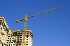 Skyscraper in the process of construction. Construction crane. Home construction stock photo