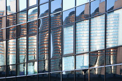 Skyscraper reflexion in windows. Buildings reflected in windows of modern office building Royalty Free Stock Image