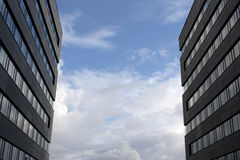 Skyscraper and skies. View at skyscraper wall and stormy skies Stock Image