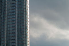 Skyscraper with Stormy Skies. Curved Glass Office Building with Grey Clouds Royalty Free Stock Images