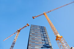 Skyscraper with tower cranes. On sky background Royalty Free Stock Photos