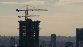 Skyscraper Under Construction In Moody Lighting. City vista with a new building under construction stock footage
