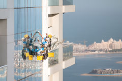 Skyscraper window cleaners wearing saftey harness at height. Window cleaners working on high rise building in Dubai Royalty Free Stock Photo
