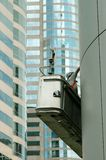 Skyscraper Worker. Worker on a outdoor conveyor cleaning the side of a skyscraper building in Central, Hong Kong stock photography