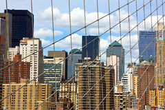 Skyscrapers. View of Manhattan skyscrapers behind cables of the Brooklyn Bridge Stock Photos