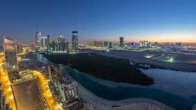 Buildings on Al Reem island in Abu Dhabi day to night timelapse from above. Skyscrapers on Al Reem and Al Maryah Island in Abu Dhabi day to night transition stock video footage