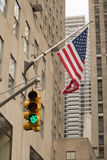 Skyscrapers, American flag and Traffic light Stock Photo