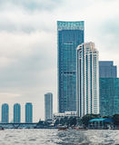 Skyscrapers, bridge and boats on river in Bangkok Stock Images