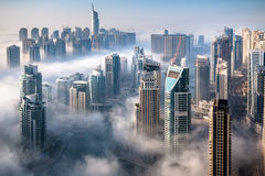 Cityscape with modern high rise buildings and dense fog clouds. Dubai skyline, an impressive aerial top view of the city in the area of Dubai Marina Royalty Free Stock Photo